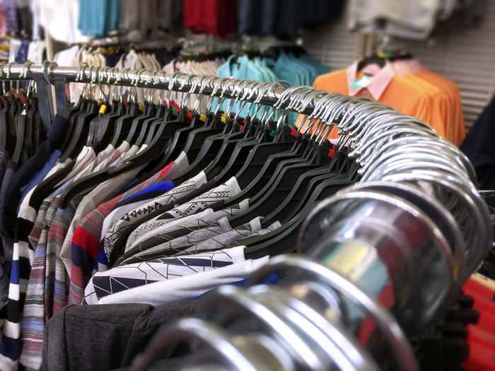Casual T-Shirts Hanging on Curved Rack Tshirt Choice Close-up Clothing Coathanger Curved  Day In A Row Indoors  Large Group Of Objects No People Textile Industry Variation