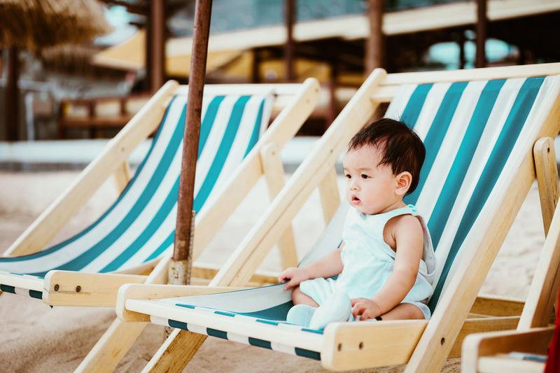 Cute baby boy sitting on chair at beach