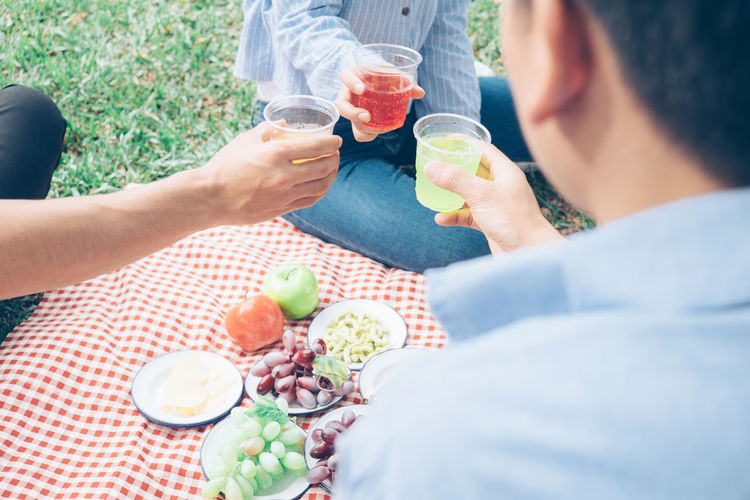 Alcohol Day Drink Drinking Drinking Glass Food Food And Drink Freshness Friendship Fruit Healthy Eating High Angle View Holding Human Body Part Human Hand Leisure Activity Lifestyles Men Outdoors Real People Refreshment Sitting Table Togetherness Women