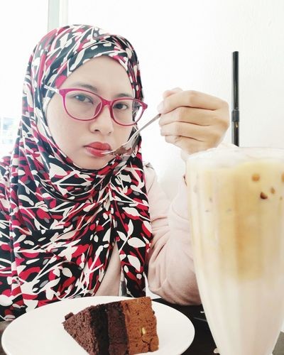 Portrait of woman wearing hijab while having dessert at table