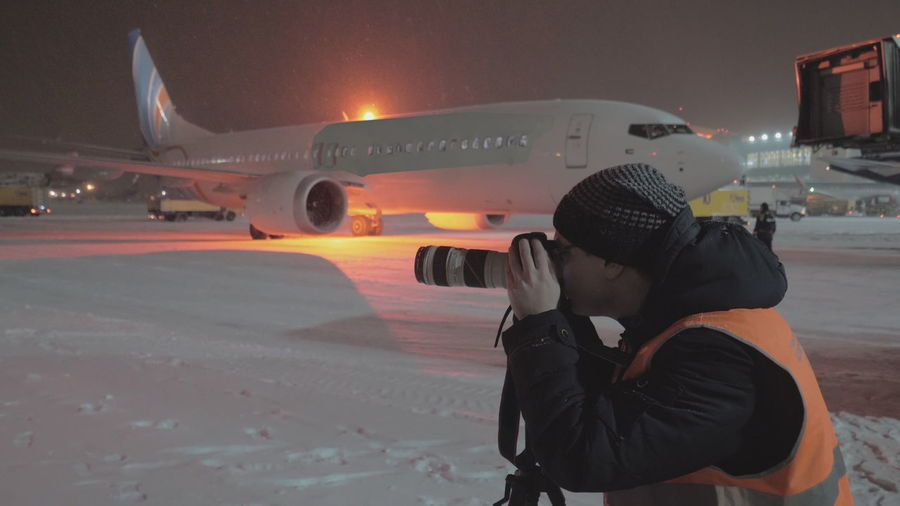 Rear view of man at airplane against sky during winter