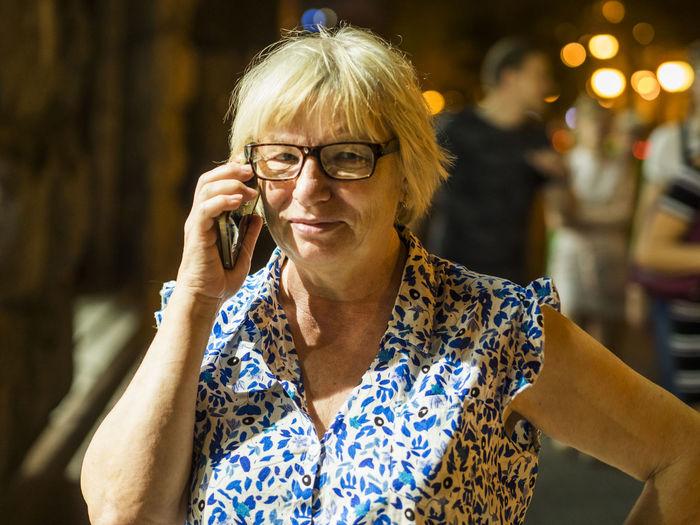 Light falling on senior woman talking on mobile phone at night