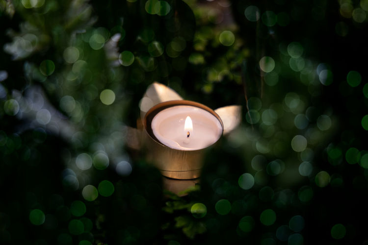 High angle view of illuminated tea light candle with green background