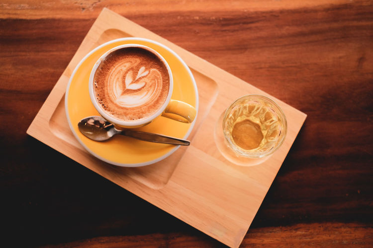 Yellow cup of Hot coffee in break time at cafe , film look effect image tone. Table Food And Drink Drink Coffee - Drink Refreshment Coffee Coffee Cup Mug Cup Latte Cappuccino Hot Drink Freshness Frothy Drink