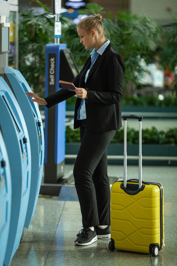 Full length of businesswoman using kiosk by luggage