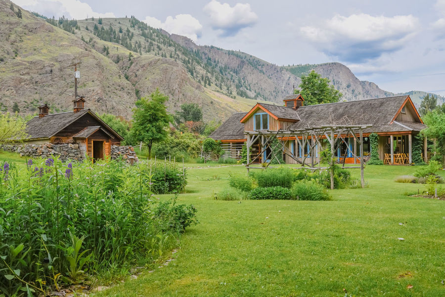 Keremeos, British Columbia/Canada - June 3, 2017: gardens, historic cellar, and restaurant building at The Grist Mill and Gardens Keremeos, an important heritage site dating to 1877. 1877 Afternoon Beautiful British Columbia, Canada Scenic The Grist Mill And Gardens Keremeos Travel Buildings Editorial  Gardens Grass Green Grass Heritage Site Historic Site June Keremeos Landscape Lawn Mountains Outdoors Restaurant South Okanagan Spring Tourism Tours