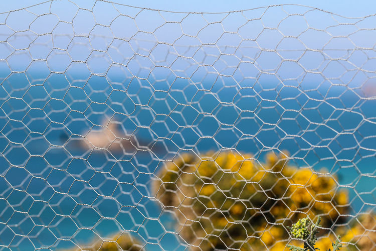 Close-up of chainlink fence against sea and sky