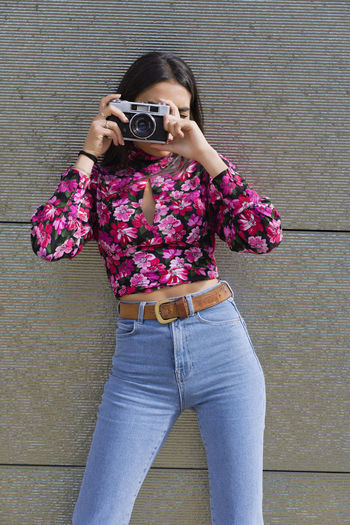 Portrait of woman photographing against wall