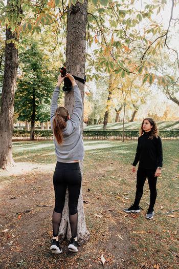 Full length of women exercising at park