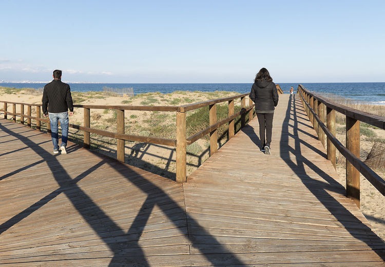Couple going by different path on a wooden walkway in Arenales del Sol de Elche, province of Alicante, Spain. Alicante Elche SPAIN Beach Beauty In Nature Clear Sky Day Full Length Horizon Over Water Men Nature Outdoors People Real People Rear View Scenics Sea Shadow Sky Standing Sunlight Water Wood - Material Wood Paneling