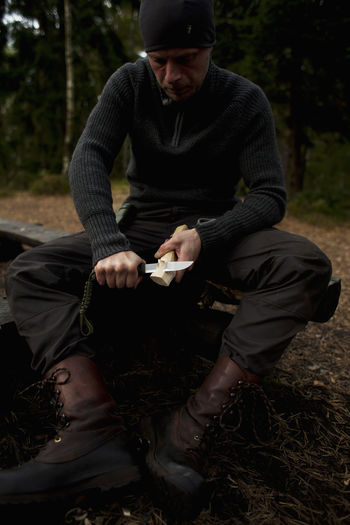 Full length of man sitting in forest