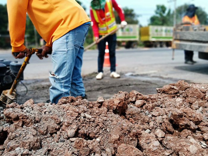 Midsection of workers digging on road