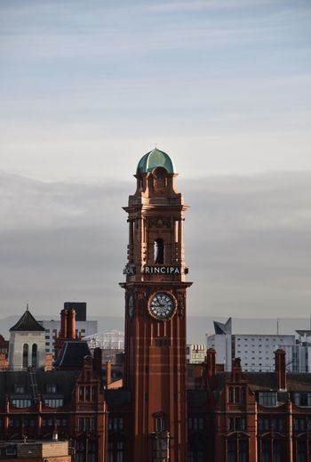 Clock tower amidst buildings in city against sky