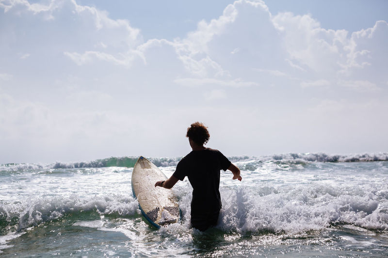 Rear view of man with surfboard in sea