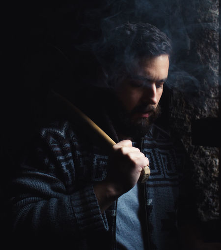 Beard Style Smoking Smoke Heritage Lumber Industry Social Issues One Person Smoke - Physical Structure Warning Sign Holding Smoking Issues Sign Young Adult Bad Habit Young Men Real People Cigarette  Smoking - Activity Activity Casual Clothing RISK Communication Lifestyles Dark Black Background