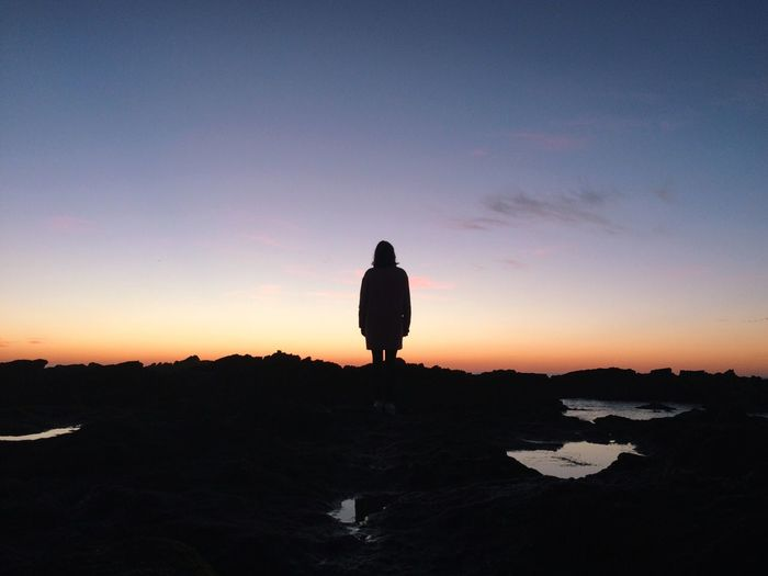 Silhouette woman standing by rocks at beach against sky during sunset