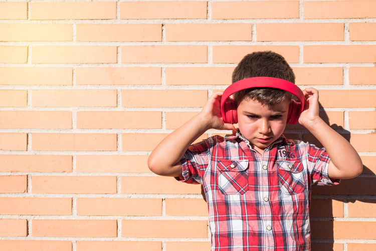 Cheerful boy listening music while standing against wall