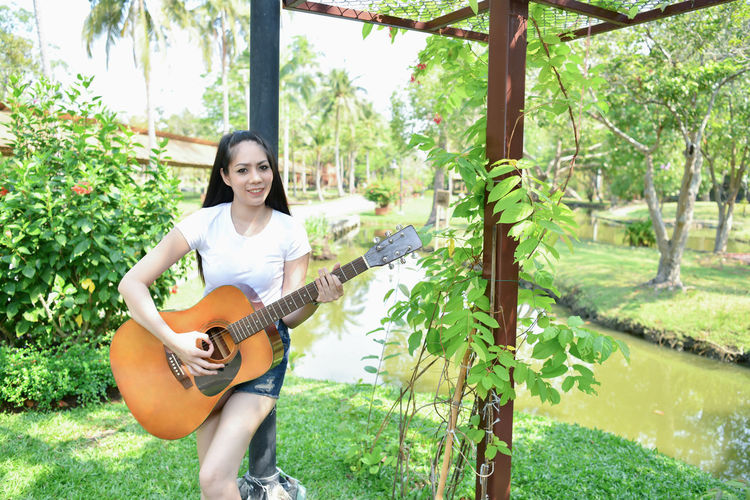 Portrait of young woman playing guitar while standing at park