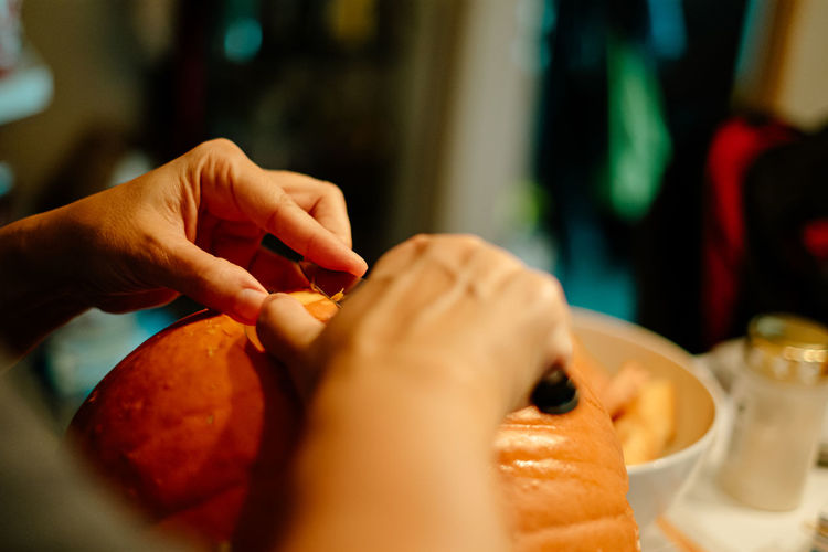Close-up of woman making jack o lantern