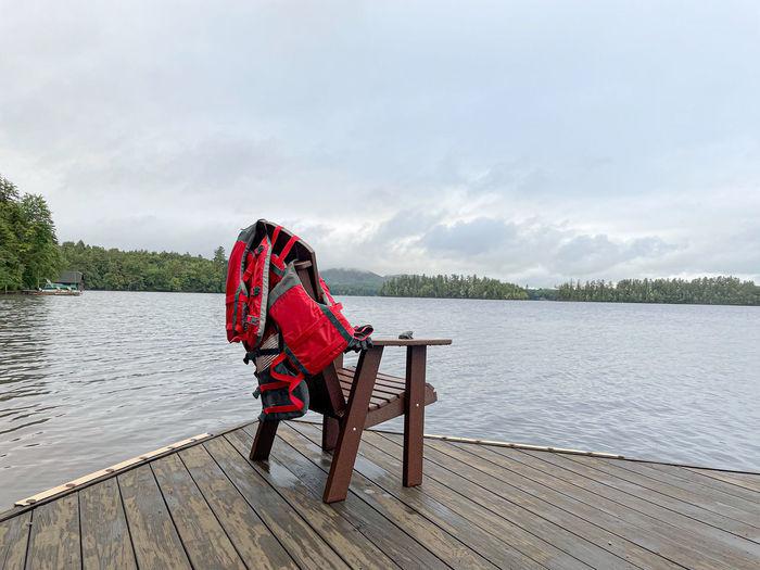 Man sitting on pier over lake against sky