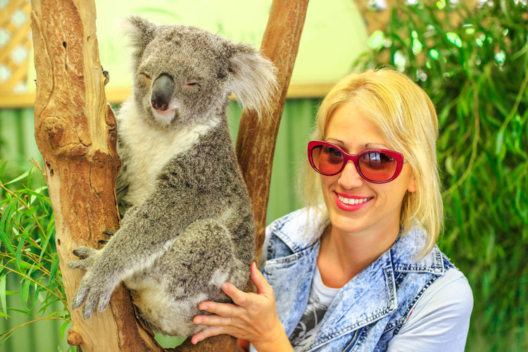 Portrait of smiling young woman with koala by tree trunk