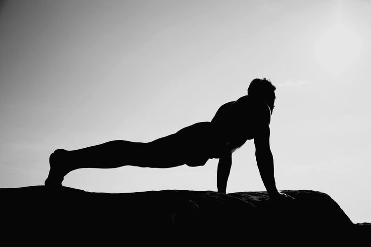 Side View Of Silhouette Man Doing Push-Ups On Rock Against Clear Sky