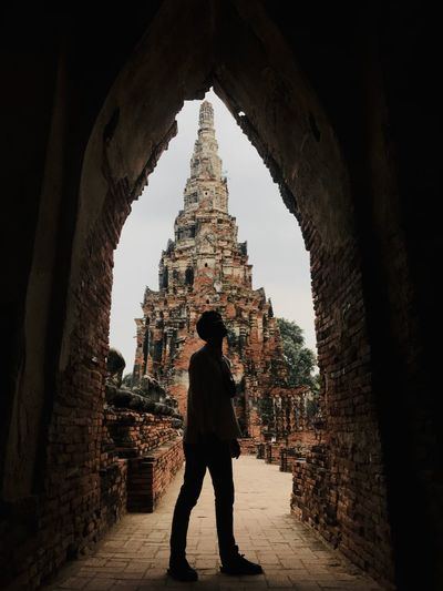 Silhouette man standing in front of ancient temple