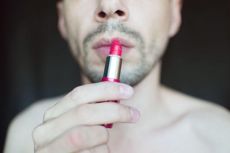 Midsection of transgender man applying red lipstick