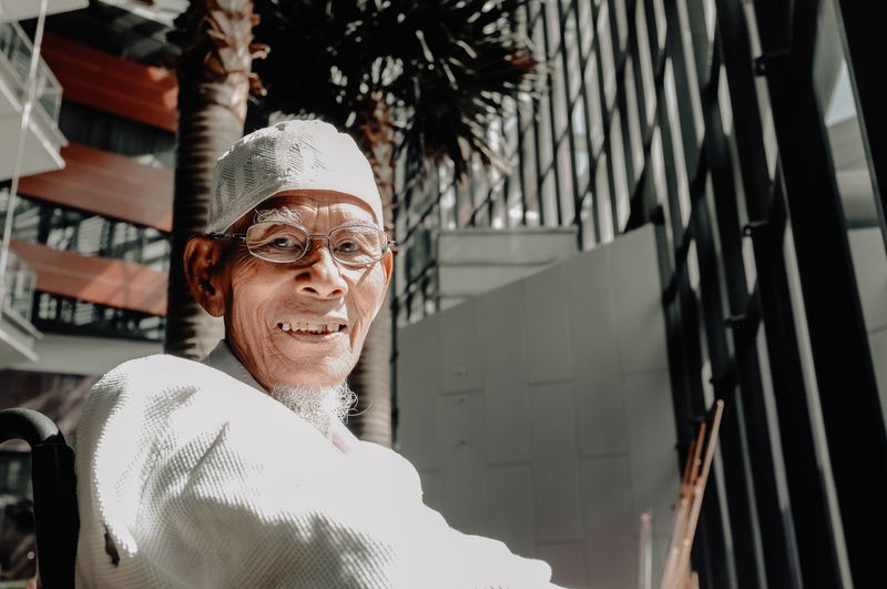 Portrait of smiling senior man wearing skull cap against building