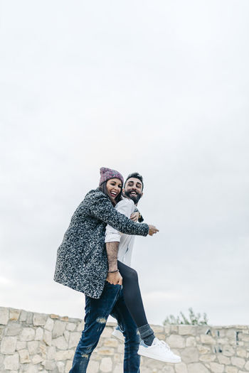 Low Angle View Of Man Giving Piggyback To Woman Against Sky