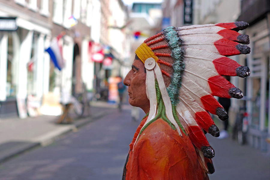 Street photography on an indian statue, Netherlands Feathers Indian Netherlands Red Skin Redskin Statue Art And Craft Character Chief Close-up Day Headdress Multi Colored Navajo Outdoors Sculpture Statue Street Photography