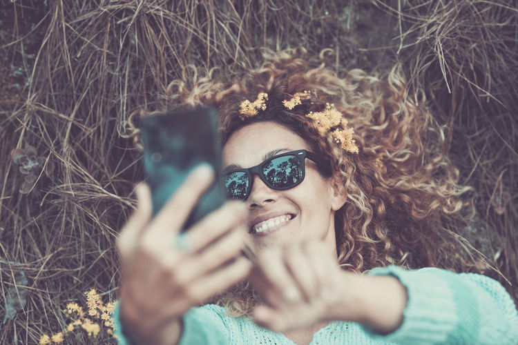 High angle view of woman taking selfie with smart phone while lying on land