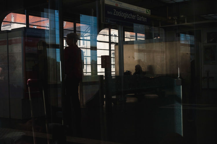 Silhouette people standing by window at railroad station