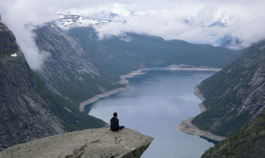 Rear View Of Man Sitting On Rock By Mountains