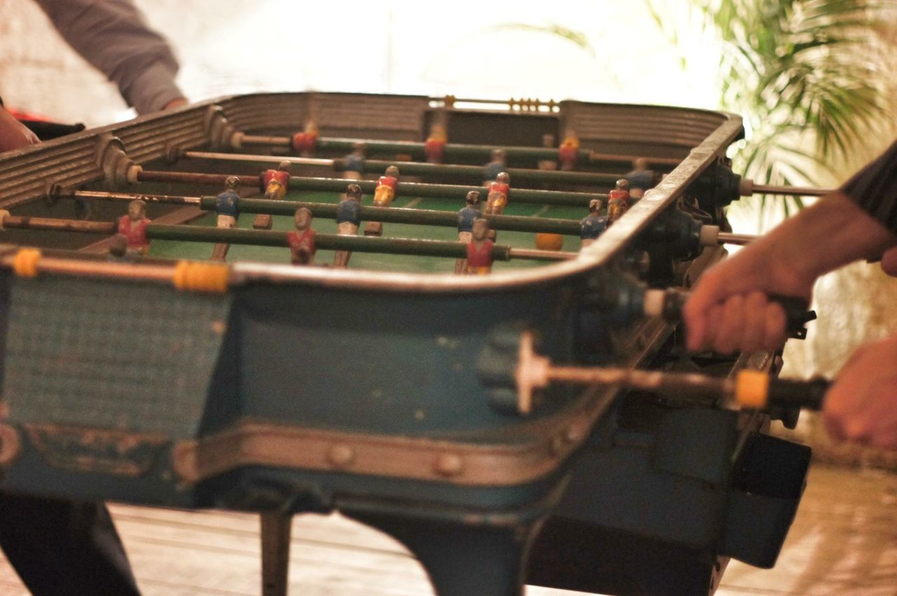 Cropped image of hands playing foosball
