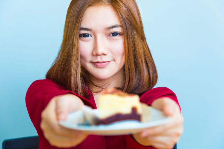 Happy young attractive Asian woman handing out a pice of chocolate and cheese cake toward the camera Asian  Coffee Woman Cake Food And Drink Handing Out  Offer One Person Special Occation  Young Adult