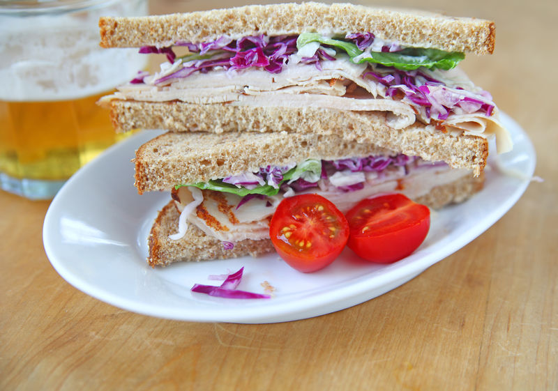 Turkey and coleslaw sandwich Beer Homemade Food Lunch Meal Natural Light Poultry Cherry Tomatoes Closeup Coleslaw Colorful Cut In Half Drinking Glass Food Freshness Healthy Eating Indoors  Lettuce Studio Shot Turkey Sandwich Vegetables White Plate Whole Wheat Bread