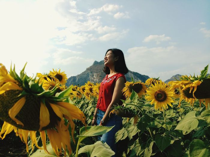Smiling woman standing by sunflower plants against sky