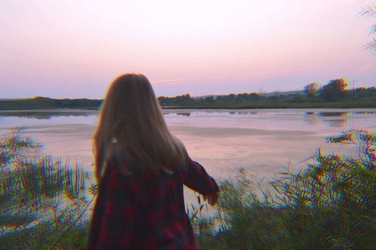 Beauty In Nature Day Lake Leisure Activity Lifestyles Long Hair Nature One Person Outdoors People Real People Rear View Reflection Scenics Sea Sky Standing Sunset Three Quarter Length Tranquil Scene Tranquility Tree Trippy Water Women