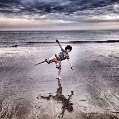 Portrait of playful boy standing on one leg at beach