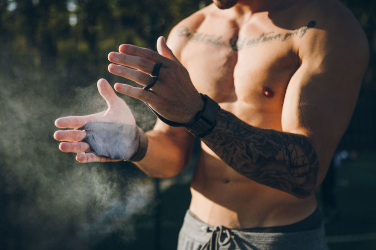 Midsection of shirtless man applying chalk on hand whiles standing outdoors