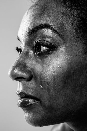 Close-Up Of Woman Crying Against Gray Background