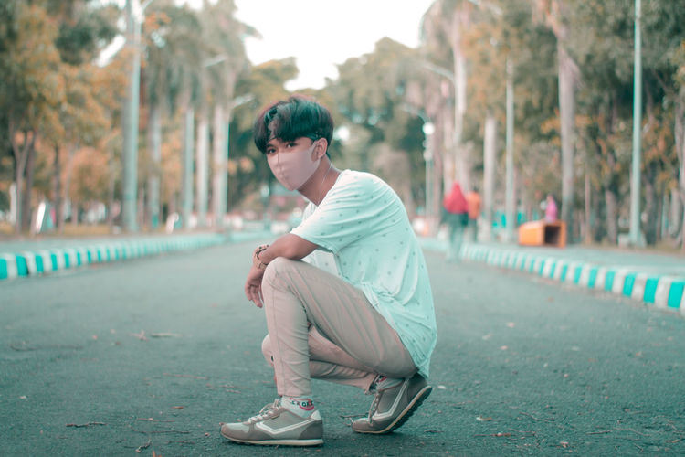 Side view of young man sitting in city