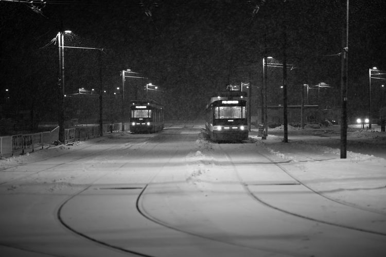 Cars on illuminated street in city during winter at night