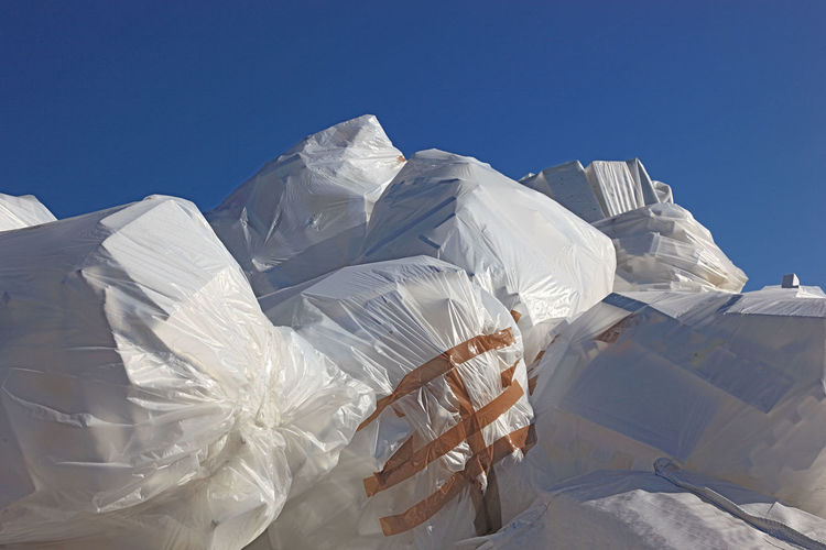 Low angle view of closed plastic bags against clear sky