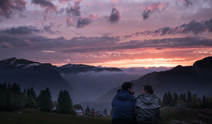 Rear view of young couple sitting against mountain range during sunset