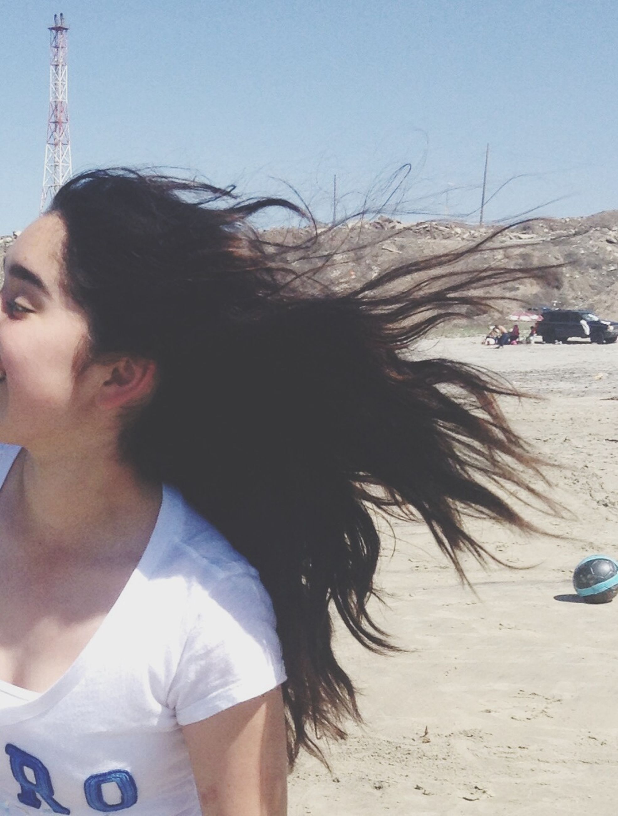 lifestyles, leisure activity, young adult, clear sky, person, casual clothing, young women, headshot, standing, long hair, day, three quarter length, outdoors, side view, waist up, sunlight, rear view