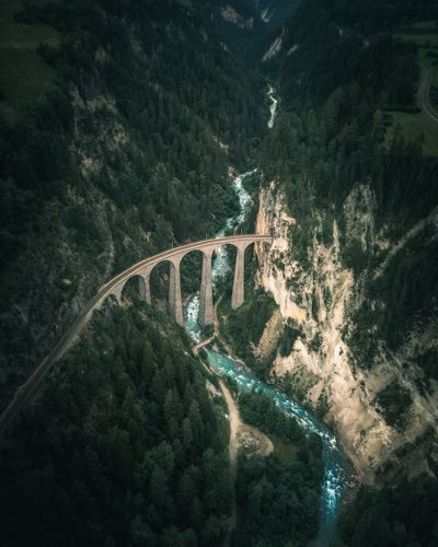 Aerial view of arch bridge over river amidst mountains