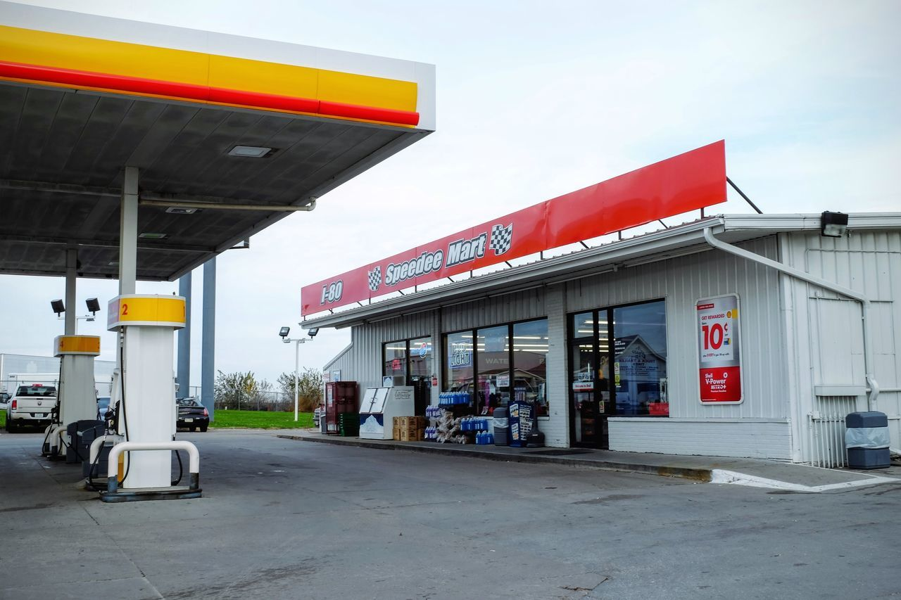 built structure, building exterior, architecture, gas station, fuel pump, text, refueling, gasoline, store, outdoors, awning, day, sky, no people