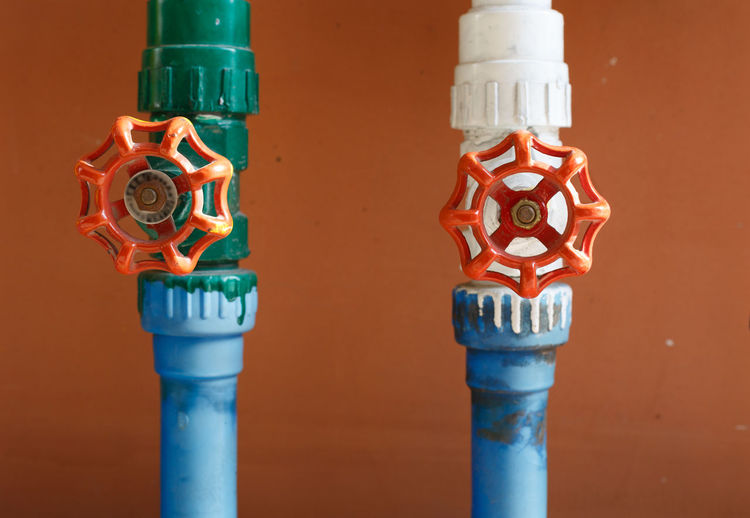 Close-Up Of Multi Colored Water Pipe Against Wall